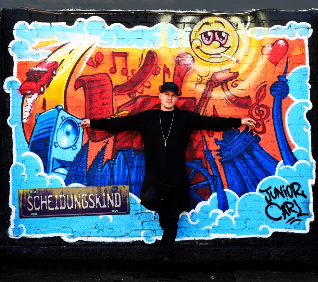 """Junior Carl vor Graffiti das Stationen und Elemente seinen Lebens ziegt. Aus dem Video """"Scheidungskind""""."""